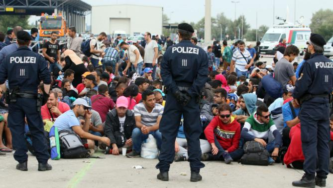 Austrian police is watching refugees after they crossed the border between Hungary and Austria in Nickelsdorf, Austria, 70 kilometers (43 miles) southeast of Vienna, Tuesday, Sept. 15, 2015. (AP Photo/Ronald Zak)