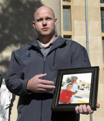 gbs111815r/ASEC -- Ken Wolter of Detroit, Michigan, a New Mexico survivor of childhood sexual abuse by Catholic Priests, at a press conference on Wednesday, November 18, 2015. Wolter holds a picture of when he was a child, and the priest, Art Perrault, who abused him. (Greg Sorber/Albuquerque Journal)