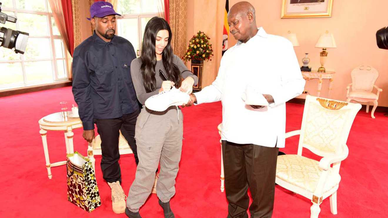 Kim Kardashian autographs a shoe for Uganda's President Yoweri Museveni as Rapper Kanye West (L) looks on when they paid a courtesy call at State House, Entebbe, Uganda October 15, 2018. Presidential Press Unit/Handout via REUTERS ATTENTION EDITORS - THIS IMAGE WAS PROVIDED BY A THIRD PARTY. - RC1C2EE08900